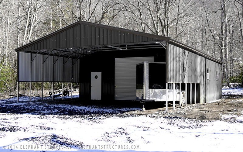 Gray metal carport with attached utility garage.