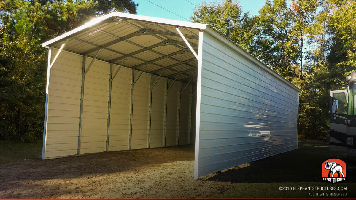 Covered carport metal building with vertical roofing and closed walls.