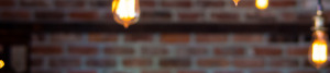 Out of focus exposed bulbs with exposed bricks in the background.