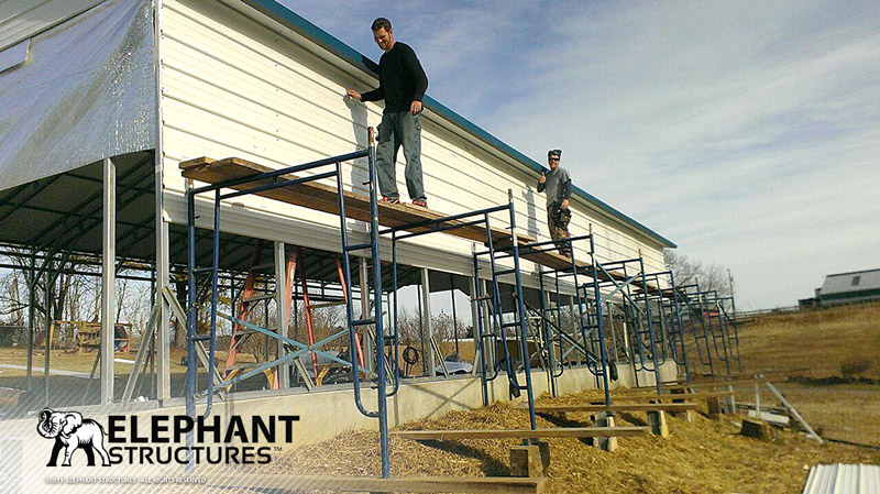 Metal carport construction with crew standing on scaffolding.
