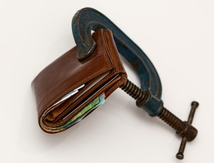 Wallet held closed by a clamp, symbolizing credit being squeezed out.
