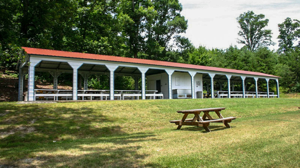 Eleven bay carport pavilion with picnic tables shown underneath