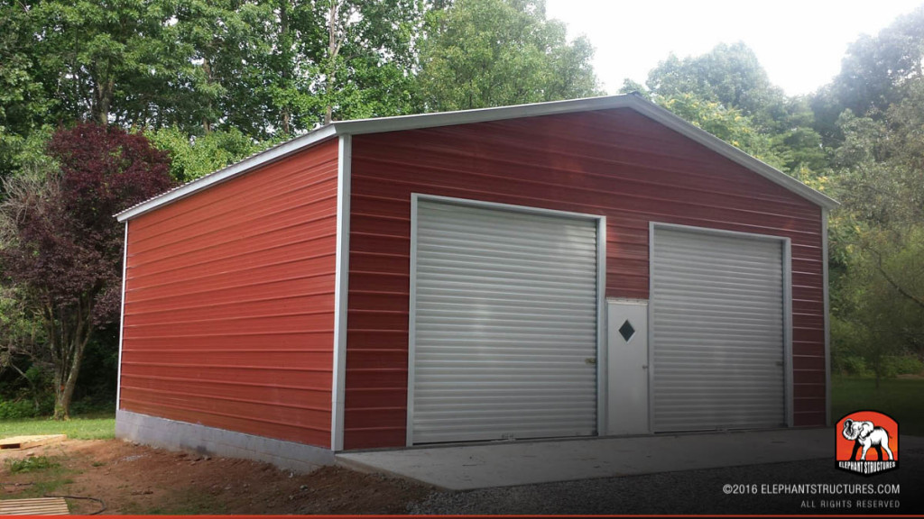 Two roll up garage doors on the front end of a metal building and one walk in door.